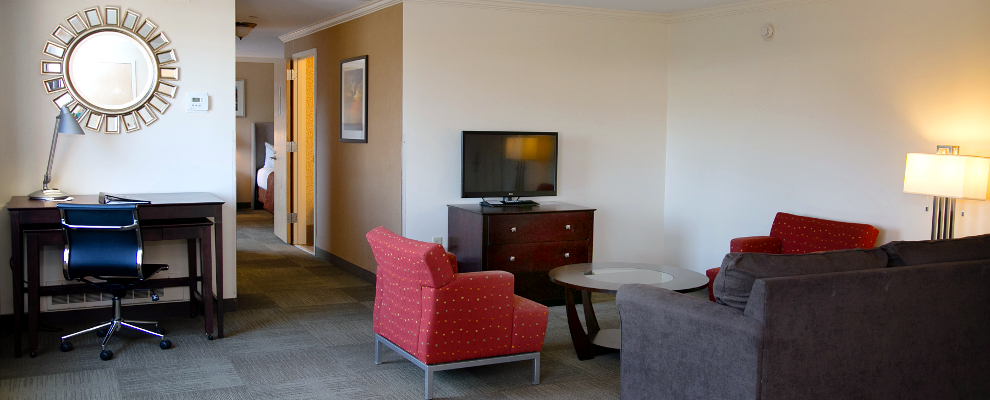 Our Club Queen Suite comes with a working desk, large TV and a spacious living area
