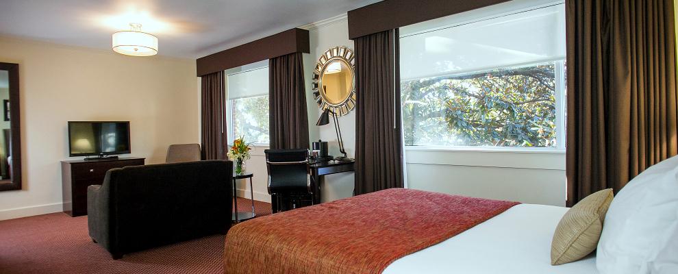 Regency Queen Suite bedroom at the UGA Hotel